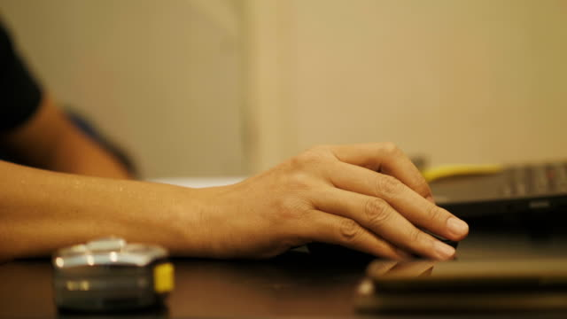 Close up of man's hand while using computer mouse with his work process