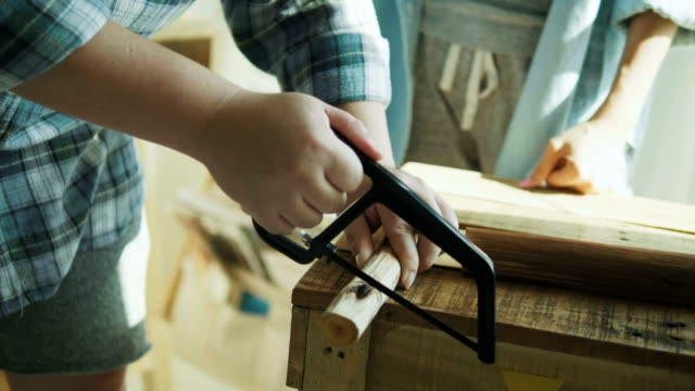 Close up of man's hand working of sawing wood in workshop class-small business concept