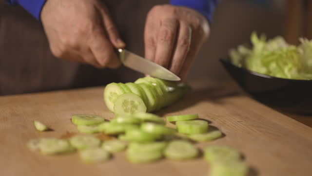 vídeos de stock, filmes e b-roll de feche as mãos do homem enquanto corta pepino na tábua de corte - braço humano