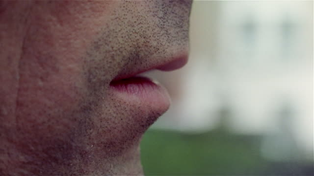 Close up of man's lips as he exhales cigarette smoke and lifts cigarette to mouth