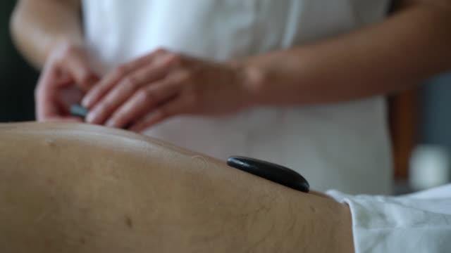nahaufnahme der masseurin, die heiße steine des kunden auf den rücken legt - verwöhnen - hausbesuch stock-videos und b-roll-filmmaterial