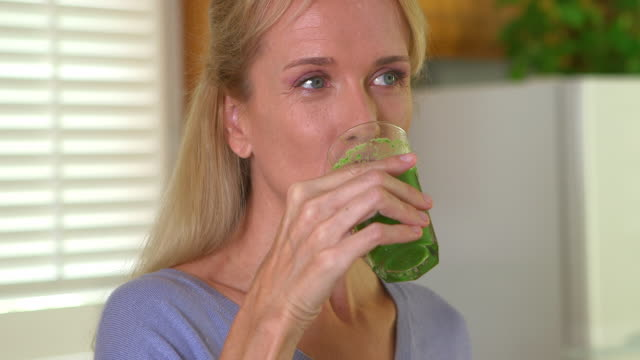 Close up of mature adult woman drinking juice