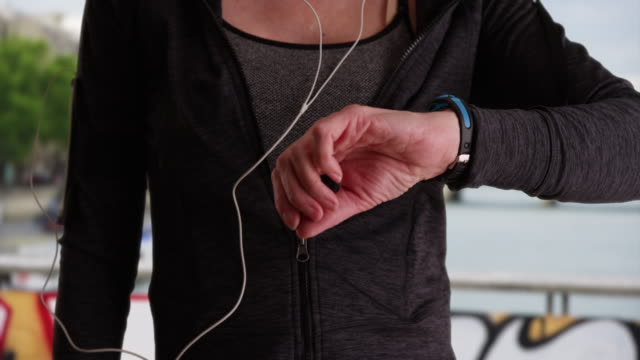 stockvideo's en b-roll-footage met close up of mature female jogger using activity tracker - jogster
