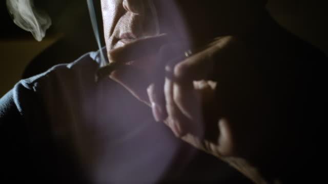 Close up of mature man lighting and smoking joint.