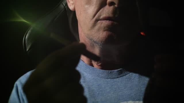 Close up of mature man smoking joint.