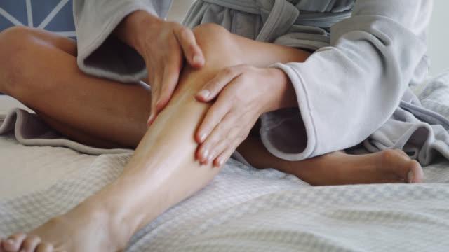 vidéos et rushes de close up of mature woman applying moisturiser to her leg. - jambe