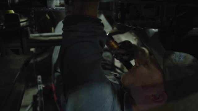 close up of mechanic laying under truck using flashlight / aurora, utah, united states - mechanic stock videos & royalty-free footage