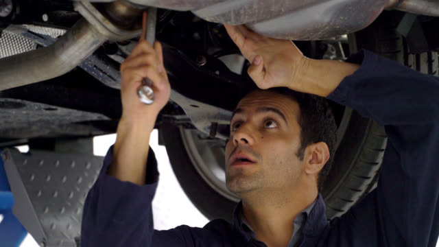 close up of mechanic working under a car using a tool and adjusting something - repair garage stock videos & royalty-free footage