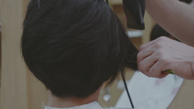 close up of men hairdresser using hair dryer and round brush while drying hair. - unrecognizable person stock videos & royalty-free footage