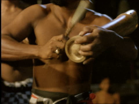 close up of men playing bamboo cylinders with sticks / Ubud / Bali / Indonesia