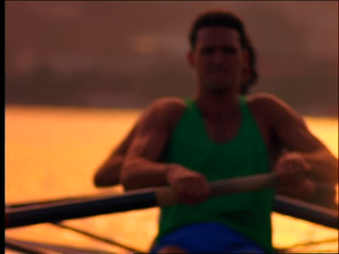 close up of men rowing in crew boat + raising arms in victory / Filter