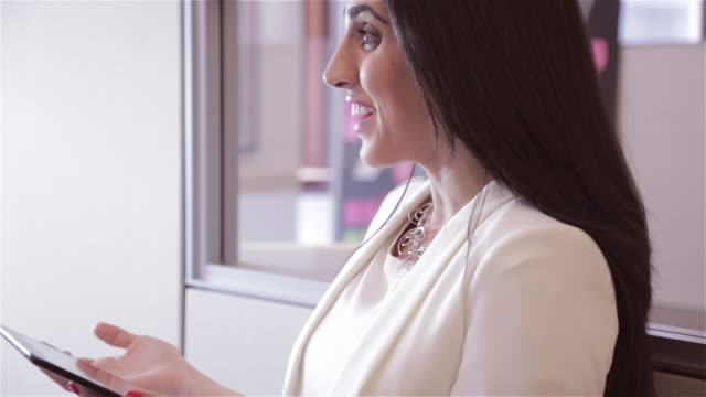 Close up of Middle Eastern female business executive telling funny story to colleagues while working on digital tablet