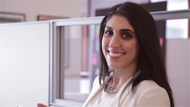 Close up of Middle Eastern female executive smiling at camera and talking with colleague