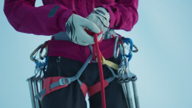 close up of midsection of ice climber securing rope to harness / palmer, alaska, united states - imbracatura di sicurezza video stock e b–roll