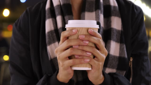 vidéos et rushes de close up of millennial black female holding coffee cup outdoors in evening - cool