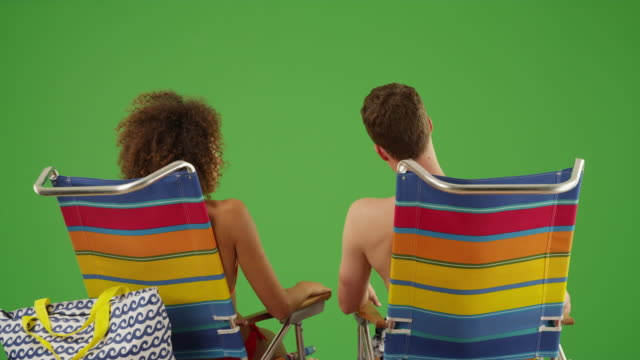 close up of mixed race couple in beach chairs on green screen - 椅子点の映像素材/bロール