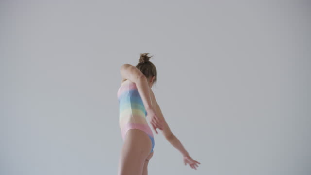 close up of modern dancer dancing in studio wearing rainbow leotard - gymnastikanzug stock-videos und b-roll-filmmaterial