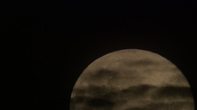 close up of moon rising in the night sky, passing wispy clouds - wispy stock videos & royalty-free footage