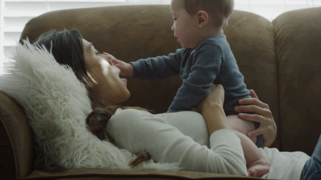 stockvideo's en b-roll-footage met close up of mother and baby son cuddling on sofa / provo, utah, united states - provo