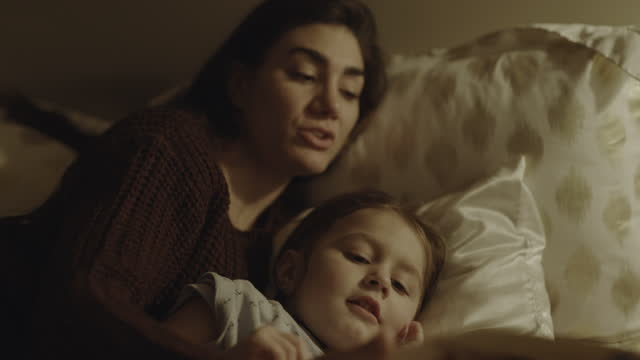 close up of mother cuddling and reading bedtime story to daughter / south jordan, utah, united states - bedtime stock videos & royalty-free footage