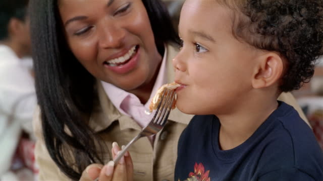 close up of mother feeding pizza to son sitting on lap in pizza restaurant - cheese stock videos & royalty-free footage