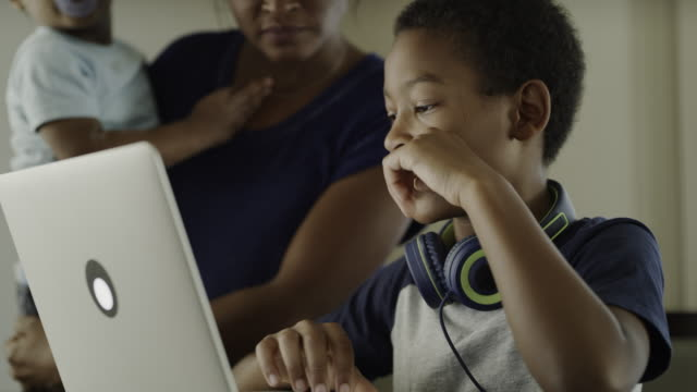 close up of mother helping boy using laptop / orem, utah, united states - family with two children stock videos & royalty-free footage