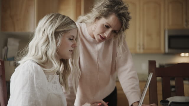 vidéos et rushes de close up of mother helping daughter using laptop in kitchen / lindon, utah, united states - teenage girls