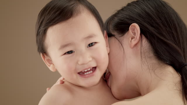 Close up of mother hugging and playing with baby boy (5-6 months)