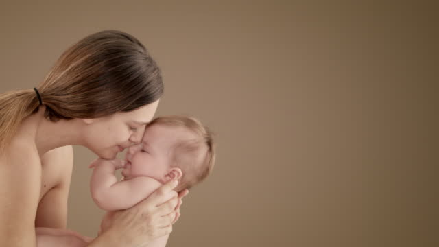 close up of mother kissing and playing with baby girl (5-6 months) - halbbekleidet stock-videos und b-roll-filmmaterial