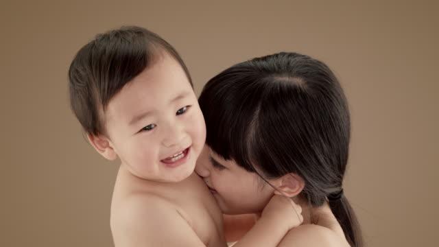 vidéos et rushes de close up of mother kissing baby boy (5-6 months) - affectueux