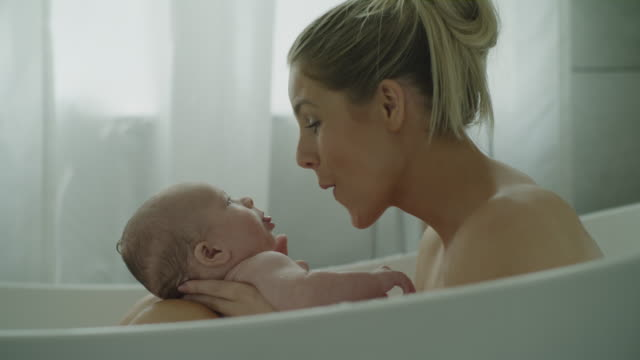close up of mother playing with baby son in bathtub / lehi, utah, united states - domestic bathroom stock-videos und b-roll-filmmaterial