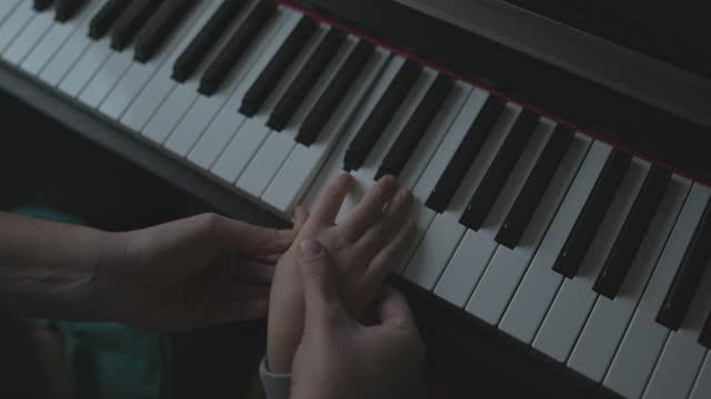 vidéos et rushes de fermez-vous vers le haut de la main de la mère tout en retenant la main du fils et en lui enseignant à jouer du piano - 4 5 ans