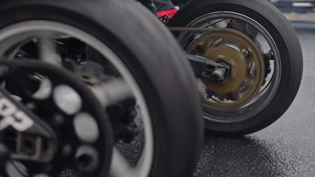 cu. close up of motorcycle wheels doing a burnout with smoke rising from the tires on an empty street - バイカー点の映像素材/bロール