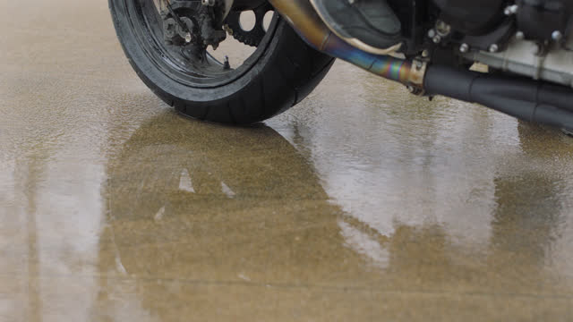 slo mo. cu. close up of motorcycle wheels doing a burnout with smoke rising from the tires on an empty street close up of a stunt motorcycle wheel on wet pavement in an empty parking lot - ノースカロライナ州点の映像素材/bロール