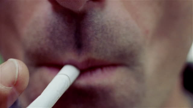 Close up of mouth of man with stubble on upper lip / bringing cigarette to mouth / smoking and exhaling smoke out of mouth