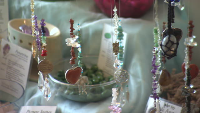 close up of newage style crystal settings / crystals and dream catcher jewellery hanging on display / close up of dream catcher with other dream... - new age stock videos and b-roll footage