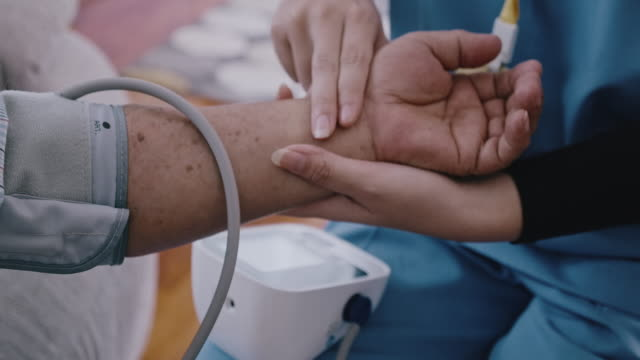 close up of nurse checking pulse and blood pressure with senior. - 70 79 years stock videos & royalty-free footage