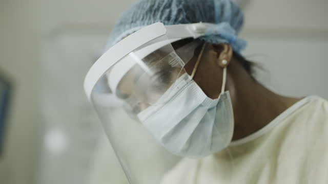 vídeos de stock, filmes e b-roll de close up of nurse wearing face shield and other personal protective equipment / salt lake city, utah, united states - autoridade
