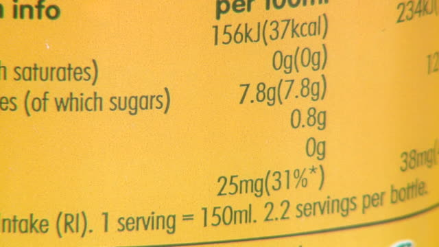 close up of nutrient label on bottle of orange juice, showing amount of sugars - healthy eating stock videos & royalty-free footage
