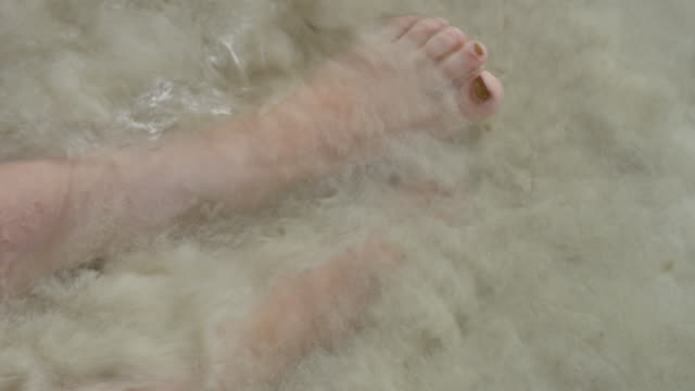 close up of ocean waves flowing over feet of woman on beach / jamesby island, tobago cays, st. vincent and the grenadines - fußkettchen stock-videos und b-roll-filmmaterial