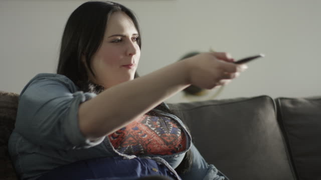 Close up of overweight woman eating snack and watching television / Orem, Utah, United States
