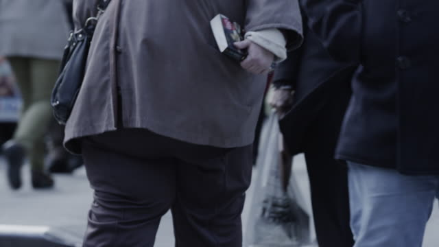 close up of overweight woman walking on bustling urban sidewalk / new york city, new york, united states - overweight stock videos & royalty-free footage