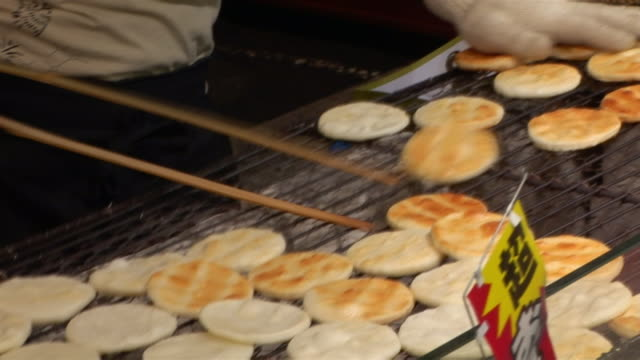 close up of pancake vendor flipping pancakes on grill at nakamise street pedestrian mall / tokyo - bancarella video stock e b–roll