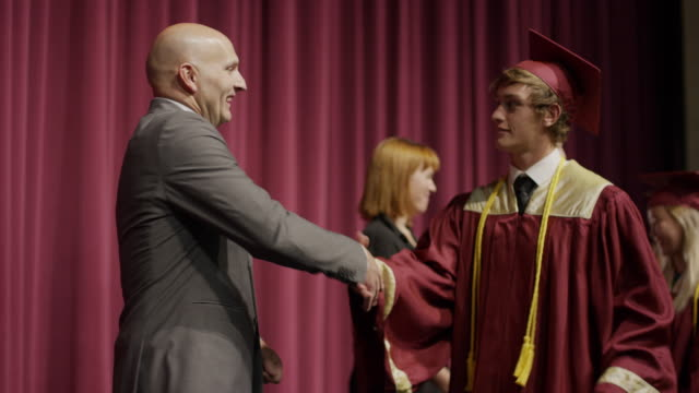 Close up of panning shot of high school graduate cheering at graduation / Mapleton, Utah, United States
