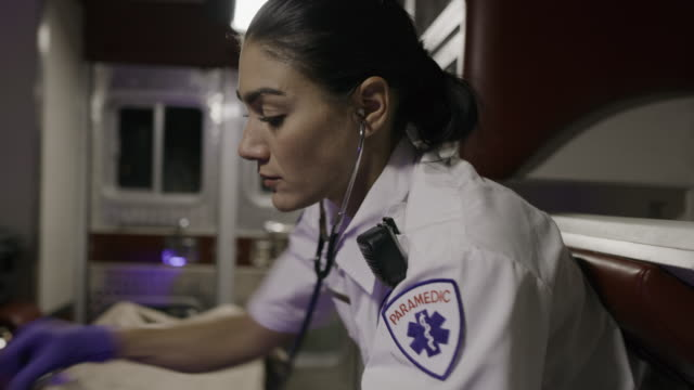 close up of paramedics listening to patient in ambulance with stethoscope / lehi, utah, united states - lehi stock videos & royalty-free footage