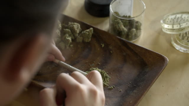 Close up of person filling rolled filtered joint.