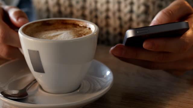 vidéos et rushes de gros personne tapant sms sur téléphone intelligent pendant une pause-café. - bring your own device