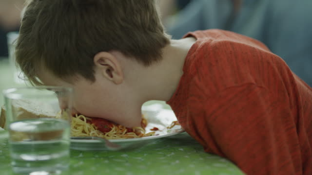 vidéos et rushes de close up of playful messy boy eating spaghetti and shaking head / lehi, utah, united states - équipement
