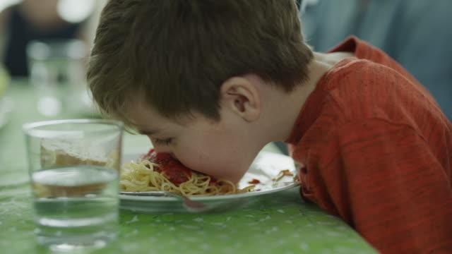 vídeos y material grabado en eventos de stock de close up of playful messy boy licking spaghetti and shaking head / lehi, utah, united states - three people