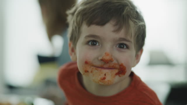 vídeos de stock e filmes b-roll de close up of playful messy boy with sauce on face looking at camera / lehi, utah, united states - filho